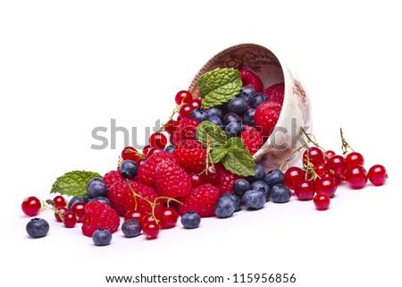 View of a bunch of tasty blueberries, red currant and raspberries isolated on a white background.