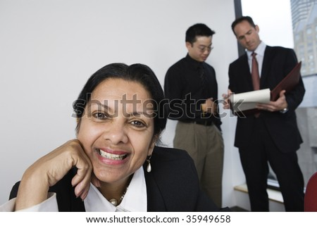 View of a businesswoman smiling with colleagues discussing paperwork in background.