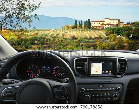 View of a car dashboard with a navigation unit traveling to Tuscany.