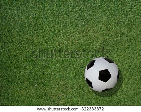 View of a classic soccer ball on green sports turf grass.