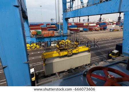 View of a container being loaded by a crane onto a freighter at a commercial port.