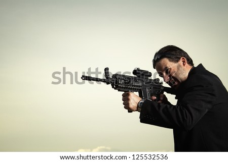 View of a contracted type killer agent wandering with a jacket and machine gun.