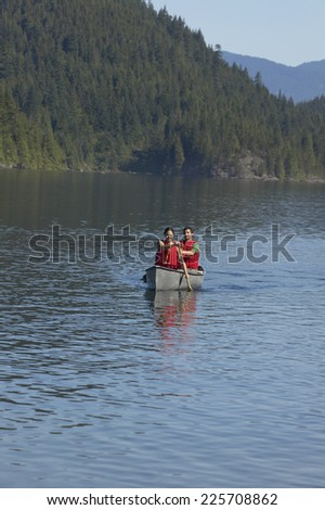 View of a couple canoeing on a lake - stock photo