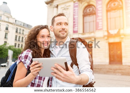 View of a Couple of young attractive tourists watching map