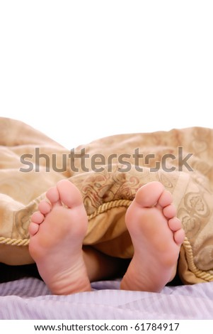 View of a couple's feet sticking out of the bed sheet while in bed - stock photo