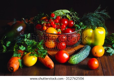 View of a delicious assortment of farm fresh vegetables and herbs  spread out on a rustic wooden table - stock photo