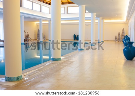 View of a deserted luxury indoor pool at a resort or health spa surrounded by pillars supporting a mezzanine - stock photo