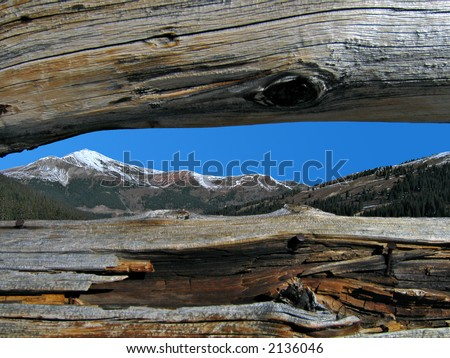 View of a distant mountain through a small crack in between two logs