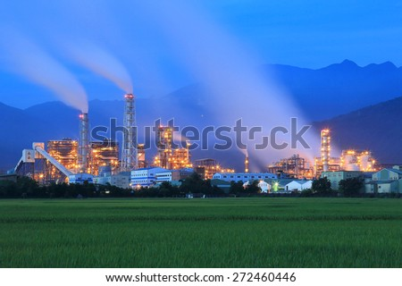 View of a factory in the middle of a green Farmland in the early morning ~ - stock photo