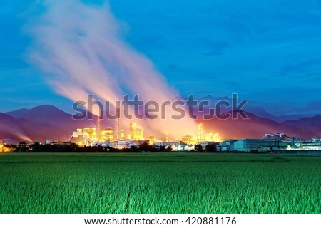 View of a factory in the middle of a green farmland in the early morning twilight ~ Factory pipes polluting air in a silent morning, a serious environmental issue - stock photo