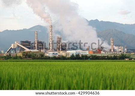 View of a factory in the middle of a green rice field in the early morning ~ Factory pipes polluting air on a silent morning, a serious environmental issue - stock photo