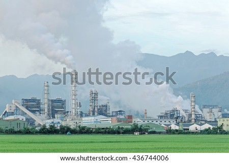 View of a factory in the middle of a green rice field in the early morning ~ Factory pipes polluting air on a silent morning, a serious environmental issue ! - stock photo