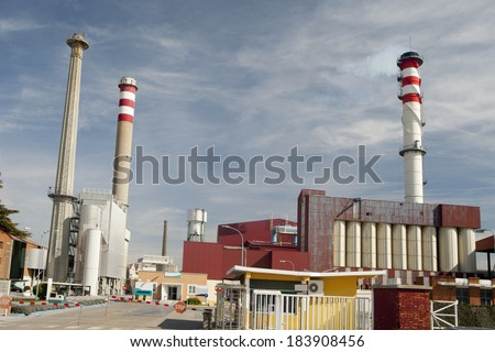 View of a factory with three tall smokestack.  Smokestacks in a factory  - stock photo