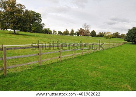 View of a Fence Running through Lush Green Farmland - stock photo