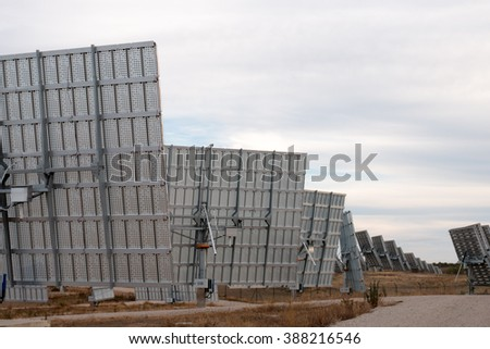 View of a field of photovoltaic solar panels gathering energy on the countryside.