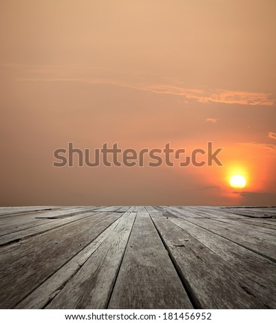 View of a fiery sunset on the horizon of an empty grungy timber deck platform.  - stock photo