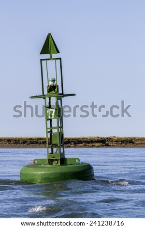 View of a floating green navigation buoy on the sea. - stock photo