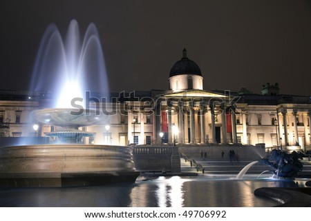 View of a floodlit National Gallery at night with fountain in foreground
