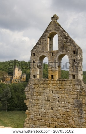 View of a French castle across the valley with a ruined church in the foreground