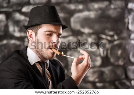 View of a gangster man is smoking a cuban cigar. - stock photo