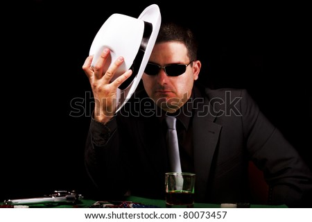 View of a gangster man playing some cards and poker, holding a white hat. - stock photo