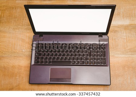 View of a grey laptop on wood desk
