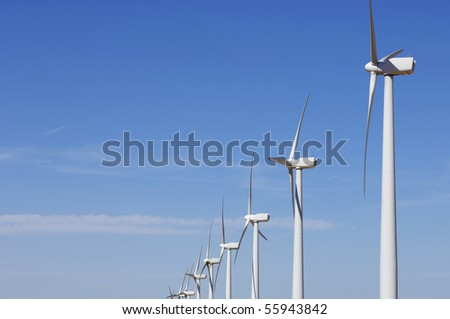 view of a group of windmills lined with blue sky - stock photo