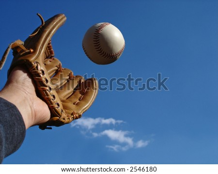 View of a hand in baseball glove reaching out to make the catch. - stock photo