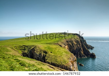 View of a headland with a lighthouse jutting into the sea on the Mull of Galloway, South West Scotland on a summer day - stock photo