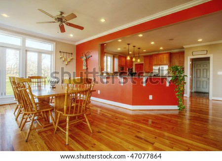 View of a home's dining area with hardwood floors. A kitchen is in the background. Horizontal format.