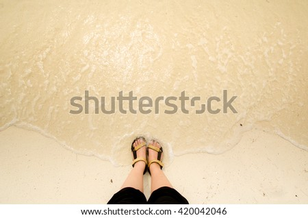 View of a human's feet at the sea shore. Top view of feet paddling in the sea with gentle ripples. Swash along beach. Concept for tropical beach, vacation, relax, morning, fresh, summer, background - stock photo