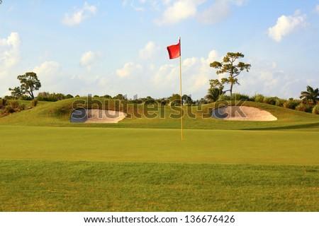 View of a landscaped golf course with flag and sand traps with cloudy sky. Horizontal shot.