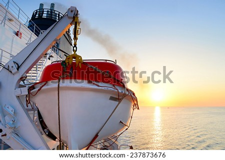 View of a lifeboat on a cruise ship at sunrise - stock photo