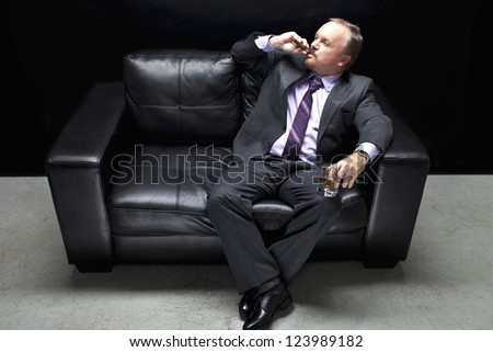View of a mafia in full suit sitting on couch and smoking cigar
