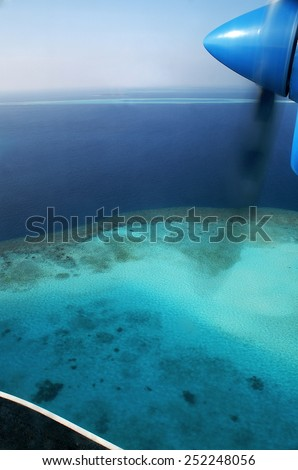 View of a Maldivian island from the seaplane with parts of the machine - stock photo