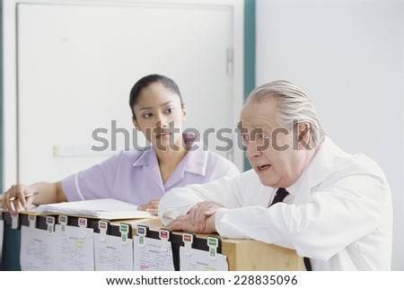 View of a male doctor arguing with a female nurse in a hospital setting - stock photo