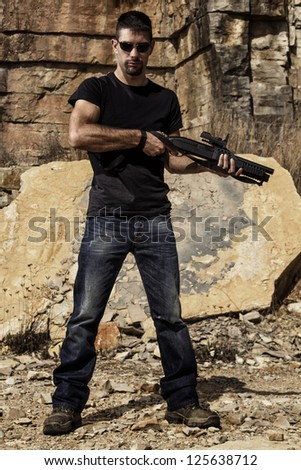 View of a man with a shotgun in jeans and black shirt on a stone quarry. - stock photo