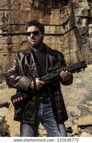 View of a man with a shotgun in jeans and jacket on a stone quarry.