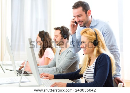 View of a Manager training a young attractive people on computer - stock photo