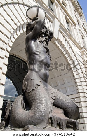 View of a merman Triton holding up a lamp outside Triton House on Finsbury Square in Islington, Central London.  The mythical Greek god is the messenger of the sea.