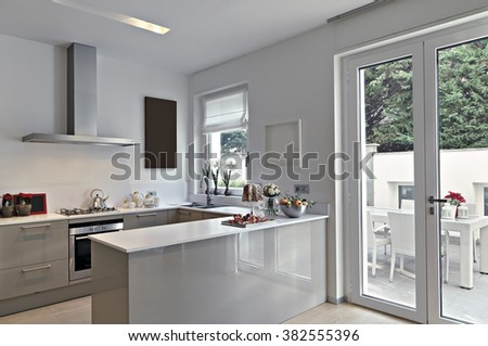 view of a modern kitchen with kitchen island overlooking on the terrace - stock photo