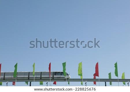 View of a monorail and flags against blue sky - stock photo