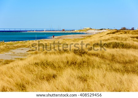 View of a part of the beach at Skanor peninsula in southern Sweden with the harbor and the bridge to Denmark of in the heat haze or shimmer. - stock photo