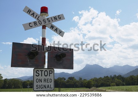 View of a 'Railway Crossing' sign with traffic lights in rural setting - stock photo