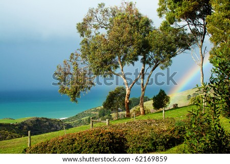 View of a rainbow over rolling green hills and ocean at Wongarra, Great Ocean Road, Victoria, Australia - stock photo