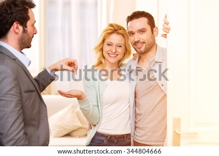 View of a Real estate agent delivers keys of new house to young couple