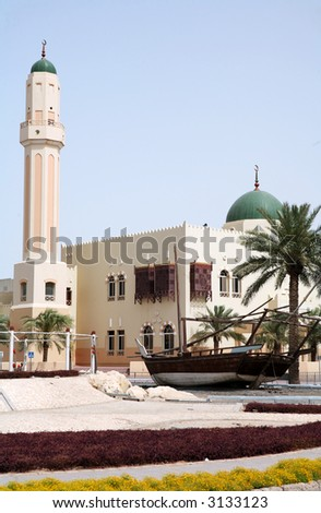 View of a recently constructed mosque in the centre of Doha, Qatar, with an old dhow in the foreground. - stock photo