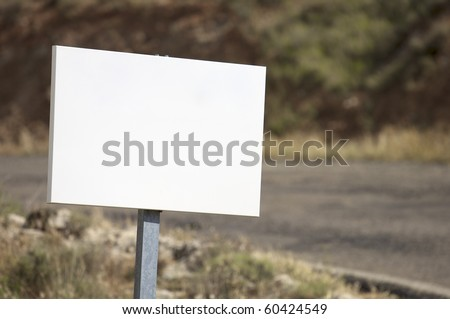 view of a rectangular white sign at the edge of a road