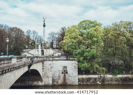 View of a river and tree lined promenade from the end of a stone bridge on a quiet afternoon - stock photo