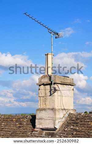 View of a Rooftop with a TV Antenna and Chimney - stock photo